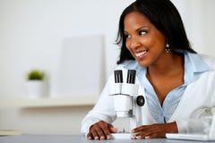 Mooie zwarte die met een microscoop werkt Stock Foto's