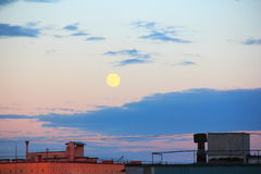 Moon above city's roofs. Moon above city's roofs in evening royalty free stock photography