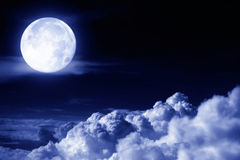 Moon above the clouds. Full moon glowing above night clouds Stock Images