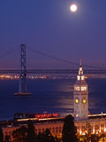 The moon above Ferry Building & Bay Bridge Royalty Free Stock Photo