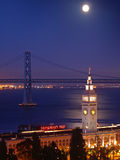 The moon above Ferry Building & Bay Bridge Royalty Free Stock Photos