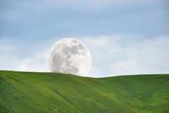 Moon above green slope Royalty Free Stock Image