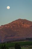 Moon above a mountain at sunset Stock Images