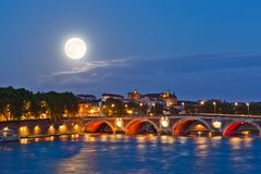 Moon above Pont Neuf. Full moon rising above illuminated ancient Pont Neuf bridge in Toulouse, France Royalty Free Stock Photos