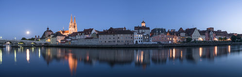 Moon above Regensburg in the evening with view to the Cathedral and stone bridge, Germany Royalty Free Stock Photography
