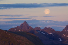 Moon above rocky peaks Royalty Free Stock Photography