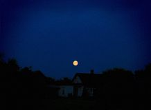 Moon above a rural lodge Royalty Free Stock Images