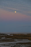 Moon above saltmarsh Stock Photo
