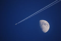 Moon and aircraft with con trail Royalty Free Stock Image