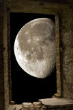 Moon through ancient stone window Royalty Free Stock Photography