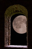 Moon through ancient stone window Stock Images