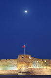 The moon and the Arad Fort during blue hours. Arad Fort is a 15th century fort in Arad, Bahrain Stock Photo