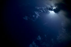 Moon behind the clouds in the night sky. Royalty Free Stock Image