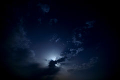 Moon behind the clouds in the night sky. Stock Photography