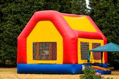 Moon bounce playhouse. A view of a colorful blow-up moon bounce playhouse in a back yard Royalty Free Stock Photos