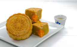 A moon cake, Chinese dessert on white plate with hot tea Royalty Free Stock Images