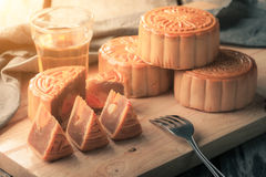 Moon cake. Chinese mid autumn festival dessert on wood board with dramatic morning scene stock photography