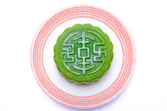 Moon-cake. Chinese traditional pastry on a white ceramic plate, with non-traditional green tea flavor royalty free stock images