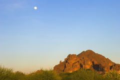 Moon and Camelback Mountain. The moon, in a blue sky, is high above red rock Camelback Mountain and green bushes well before sunset in Phoenix, Arizona Royalty Free Stock Image