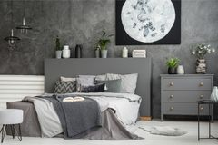 Moon canvas on a grey wall in a monochromatic cozy bedroom inter. Ior with a bed with cushions, bedding an a blanket. Real photo stock photos