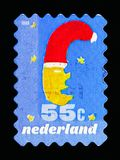 Moon with Christmas hat, December stamps serie, circa 1999. MOSCOW, RUSSIA - MAY 13, 2018: A stamp printed in Netherlands shows Moon with Christmas hat, December Stock Photo