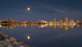 The moon and cityscape lights, reflect off harbour waters, poole Royalty Free Stock Images