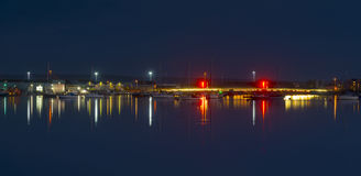 The moon and cityscape lights, reflect off harbour waters, poole Stock Photo
