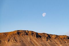 The moon in the clear blue sky over the mountain, Norilsk royalty free stock photos
