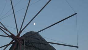 The moon and a close up of the historic windmills on mykonos. Greece stock video