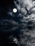 Moon and clouds above sea at night royalty free stock photos