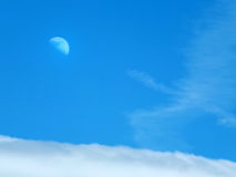 Moon and clouds in a blue summer daytime sky Royalty Free Stock Photography