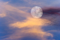 Moon Clouds Skies. Is a vibrant surreal scenic of a full moon rising amongst the colorful cloudscape Stock Photography