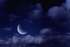 Moon in a cloudy sky Stock Image