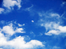 Moon in cloudy sky. The moon out during the day in a cloudy blue sky Stock Photography