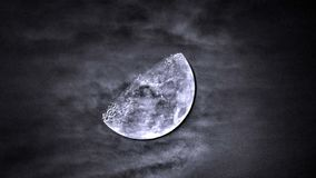 Moon in cloudy sky and dramatic dark clouds Stock Image