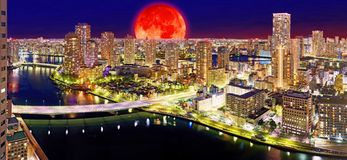 Moon collage of night Tokyo panorama with wide angle aerial view stock image