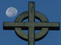 Moon and the Cross. Setting moon behind the cross of a local church Royalty Free Stock Photo