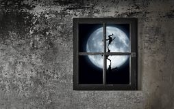 Moon Dance. Gray stone wall with 4-paned window and full moon shining through and silhouette in front of moon Royalty Free Stock Image