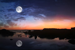 Moon in dark sky. Moon in dark blue cloudy sky after sunset Stock Photo