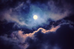 The moon on the dark sky. Among the clouds, natural abstract background Royalty Free Stock Image