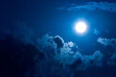 Moon in darkness. Shone circle of the moon in darkness on a background of the star sky and clouds Stock Photo