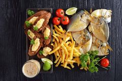 Moon fish,chips, beer and toasts on slate tray royalty free stock photo