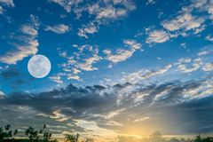 The moon is floating in the sky in the morning. The sun is rising Stock Photos