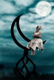 Moon and girl. A little girl sits on a half moon and writes. look portfolio there will find collection kollazh on a theme a moon Stock Photos