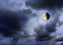 Moon glowing in the dark cloudy sky Royalty Free Stock Photos