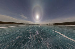 Moon halo in the night sky over Lake Baikal ice. Stereographic p Stock Photography