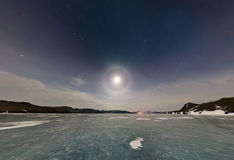 Moon halo in the night sky over Lake Baikal ice. Stereographic p Royalty Free Stock Images