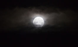 The moon in the haze of the clouds at night.  Royalty Free Stock Photo
