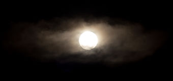 The moon in the haze of the clouds at night.  Stock Images