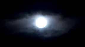 The moon in the haze of the clouds at night.  Royalty Free Stock Photography
